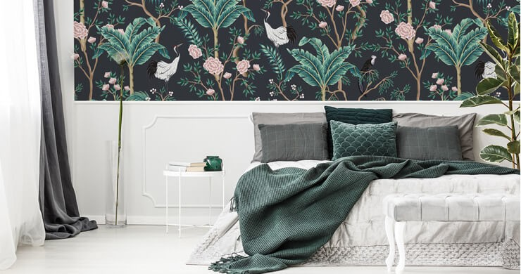 dark oriental wallpaper with birds, palm trees and roses in it in a decadent bedroom with dark green bedding