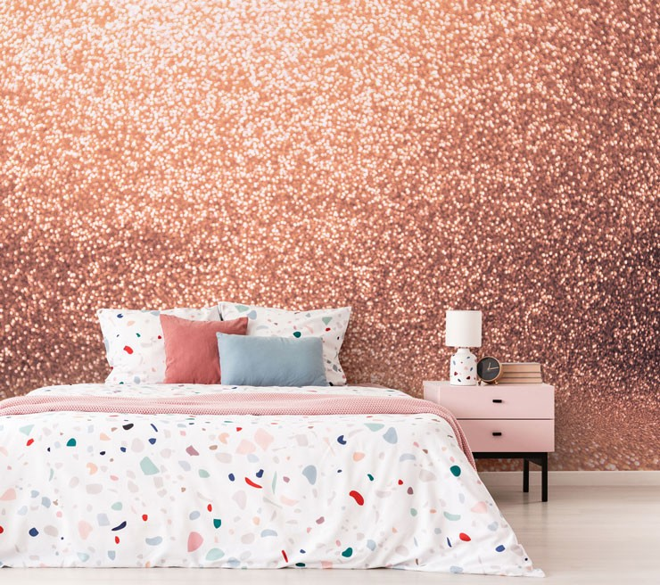 rose gold glitter effect wallpaper with terrazzo patterned bed