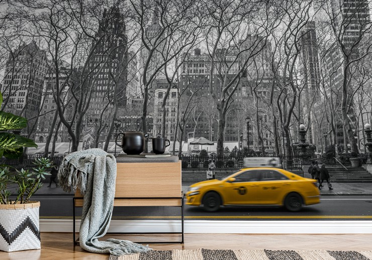 black and white photo of new york central park railing with yellow cab wallpaper in room with small table and blanket