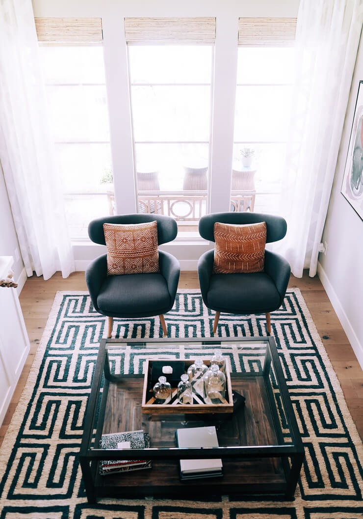 dark green and white patterned rug in cool lounge with two grey chairs