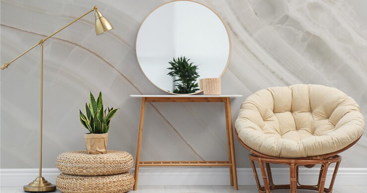 off-white lined marble wallpaper in lounge with bamboo chair with cream cushion, green plants and golden lamp and round mirror