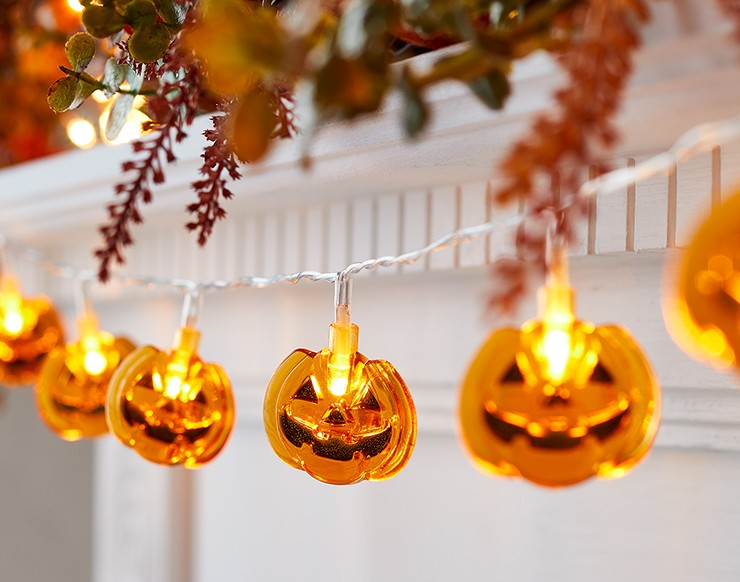 smiling orange pumpkin lights hanging from a fireplace
