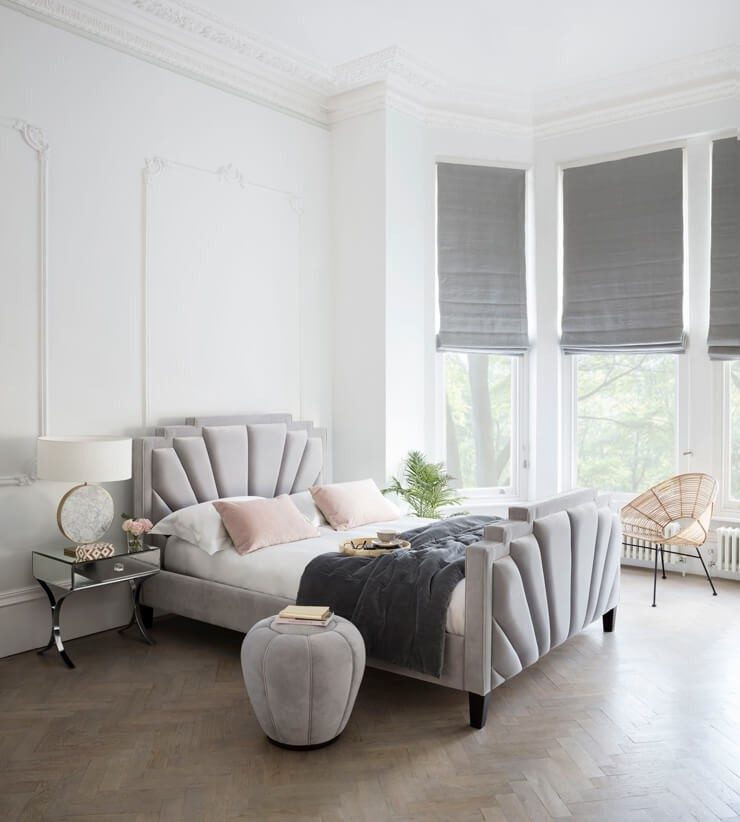 grey, white and pastel pink scalloped bed in white bedroom