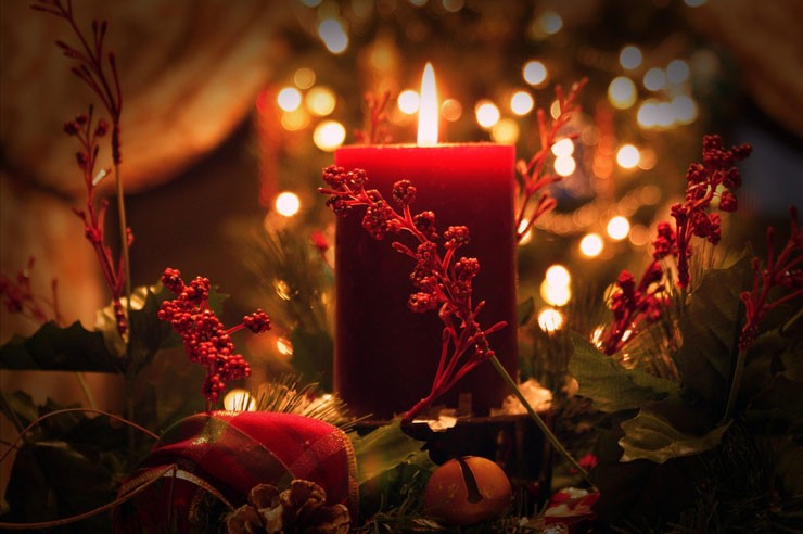 red candle lit up surrounded by faux holly, red ribbons and bells