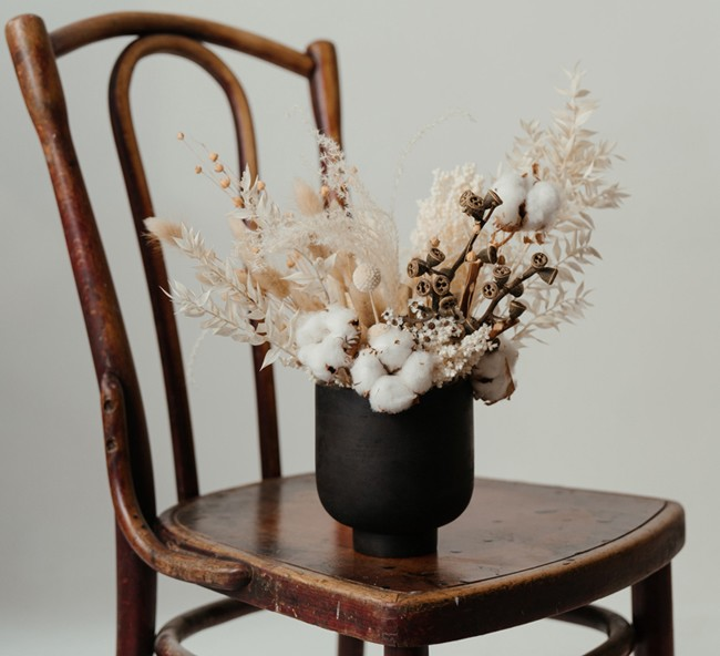dried flowers and cotton in black vase on brown wooden chair