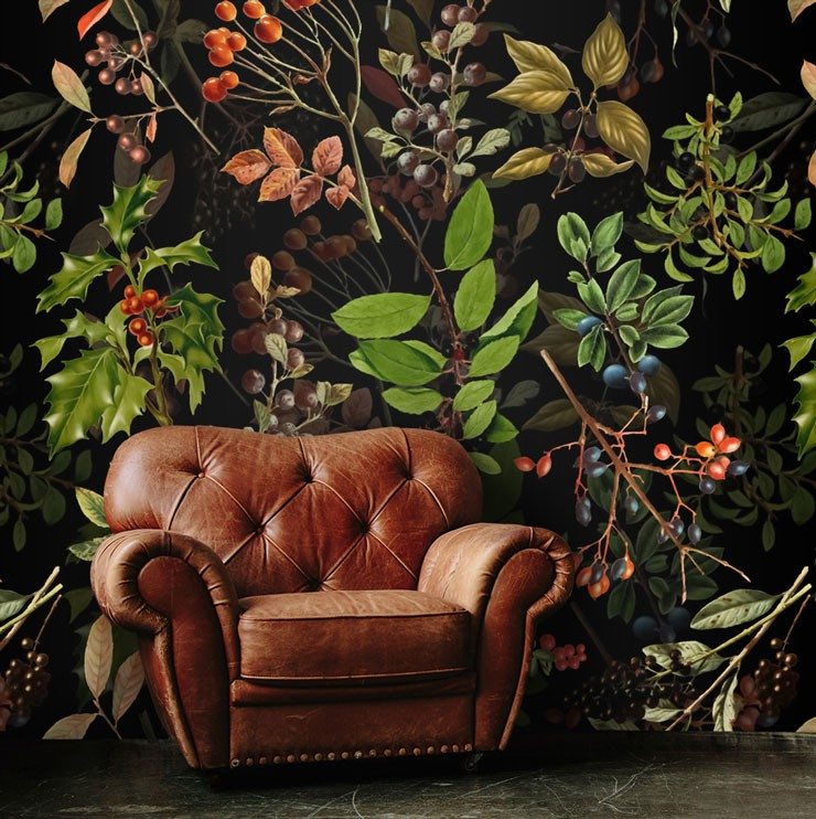 illustrated holly and green foliage on black background wall mural with brown leather armchair