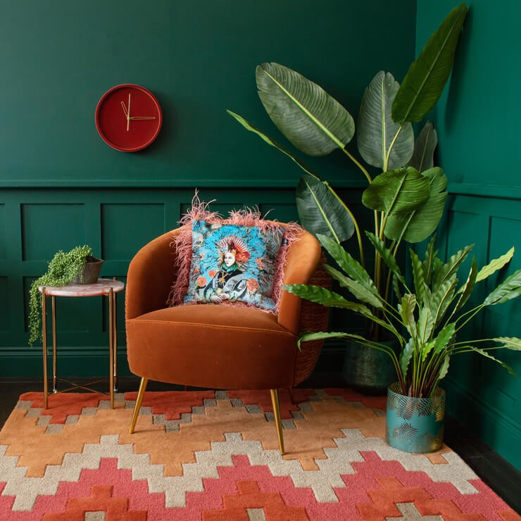 patterned orange rug with dark green panelled walls and orange chair