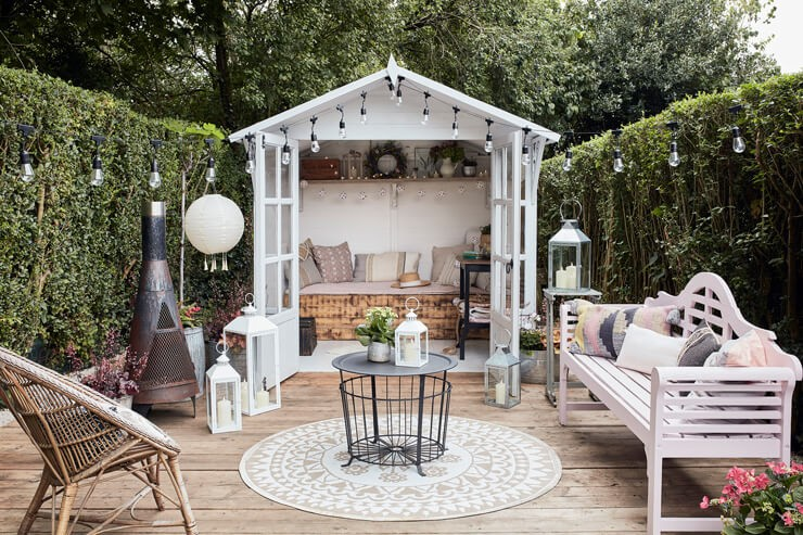 white summer house with wooden decking and beautiful accessories