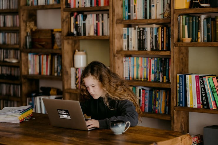 long brown haired girl with laptop with book shelves