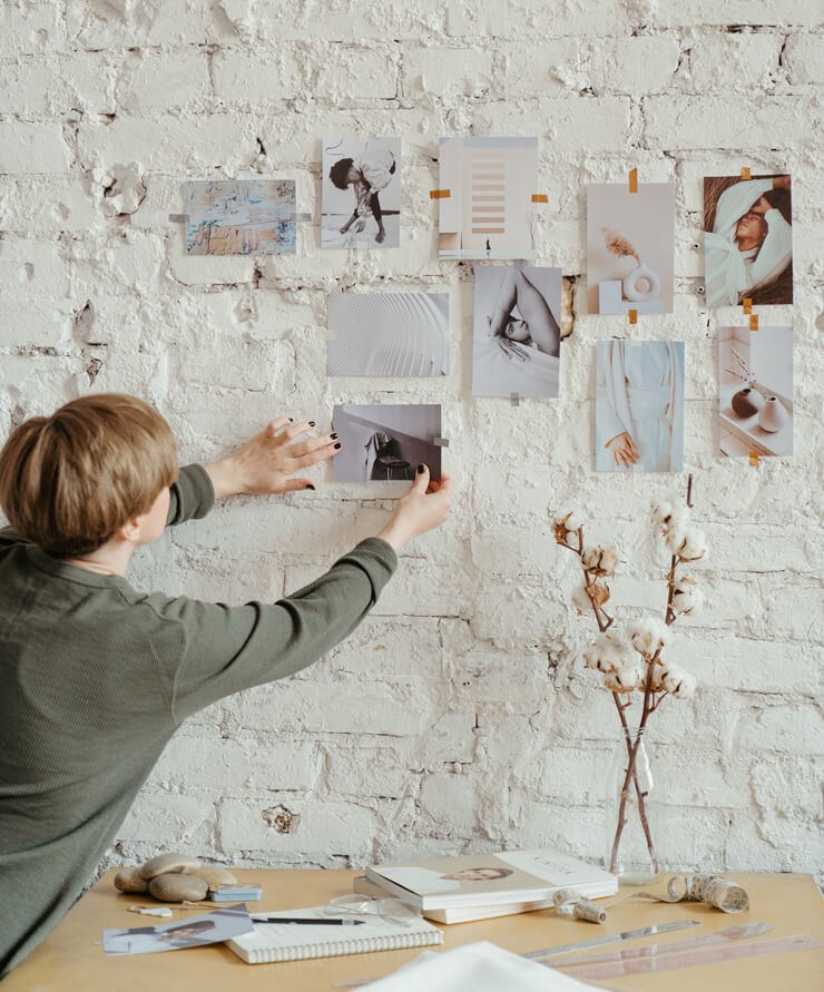 short haired woman changing photographs on her wall