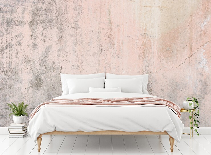 grey and pink cracked concrete wallpaper in bedroom with bed with white and pink bedding and green plant