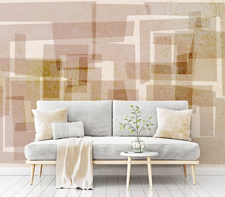 block printed brown shapes on beige background wallpaper with grey sofa with cream cushions and blanket