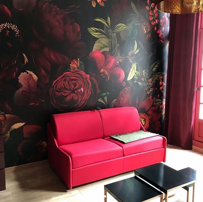 dark maroon floral wallpaper in lounge with pink sofa