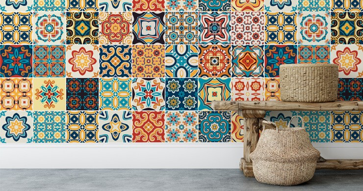 orange, blue, yellow and navy patterned tile wallpaper in room with wooden bench and rattan baskets