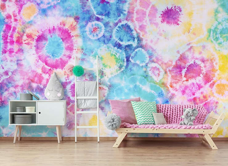 pink, blue, yellow and white tie dye wallpaper in girl's bedroom with pink sofa
