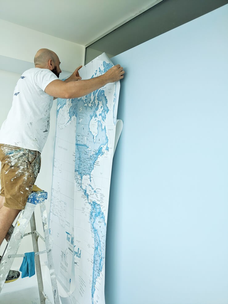 decorator installing white and blue map peel and stick wallpaper