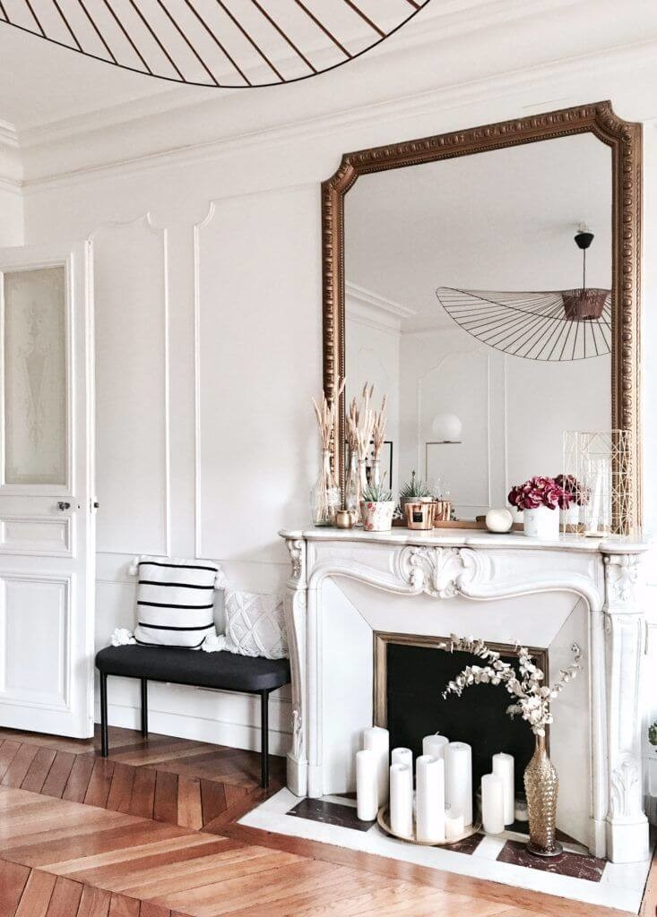 vintage styled lounge with large gold mirror above fire place