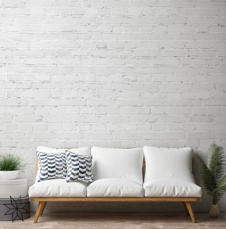 white couch with white brick wallpaper in living room