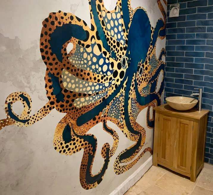 inky-blue and gold colour art deco octopus wall mural in bathroom with blue tiles to match