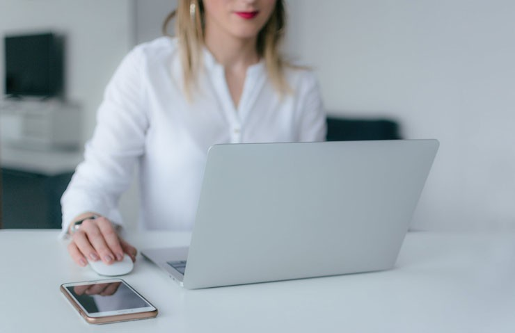 blond woman wearing a white shirt on her laptop not looking at her phone