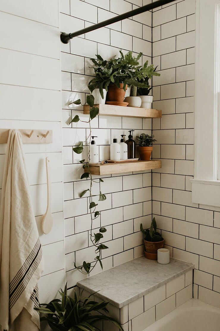 white tiled bathroom with black grouting, tropical plants and wooden and clay room accessories