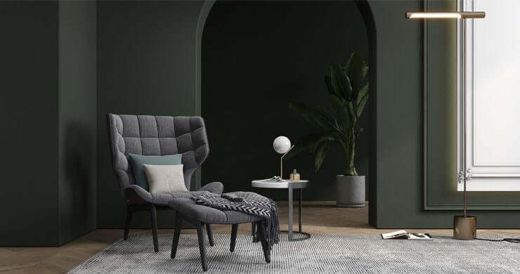living room with dark green and black walls and grey armchair and carpet