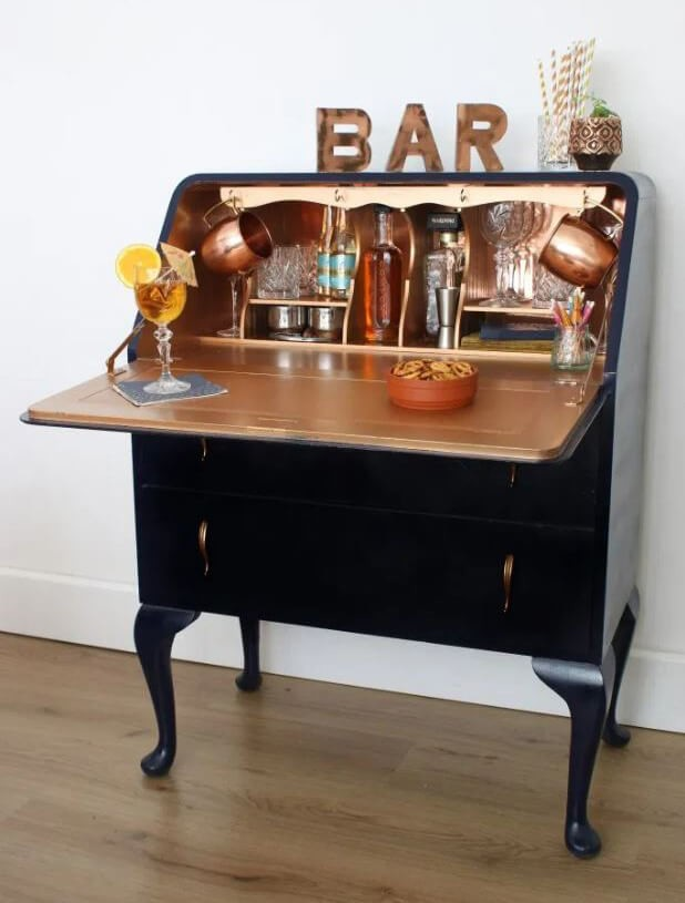 upcycled bureau in black and gold with drinks bottles inside