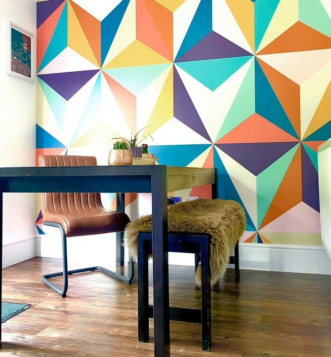 colourful retro geometric wallpaper in '70s style room with wooden table and brown leather chair