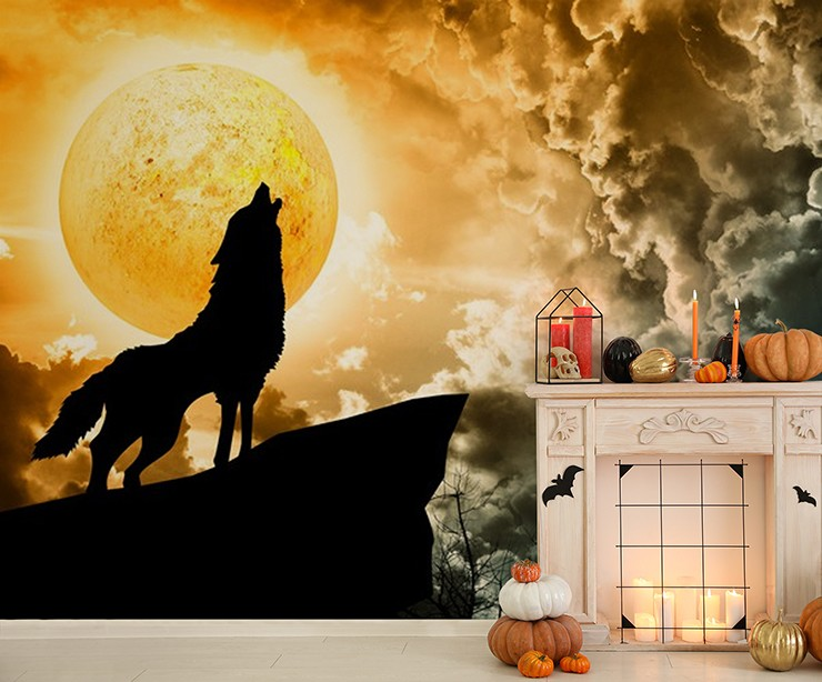 black wolf silhouette howling against orange moon mural in halloween decorated lounge with fireplace