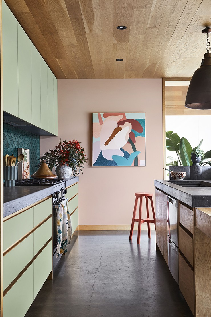 peach-pink walls in kitchen with green cabinets and abstract art work on walls