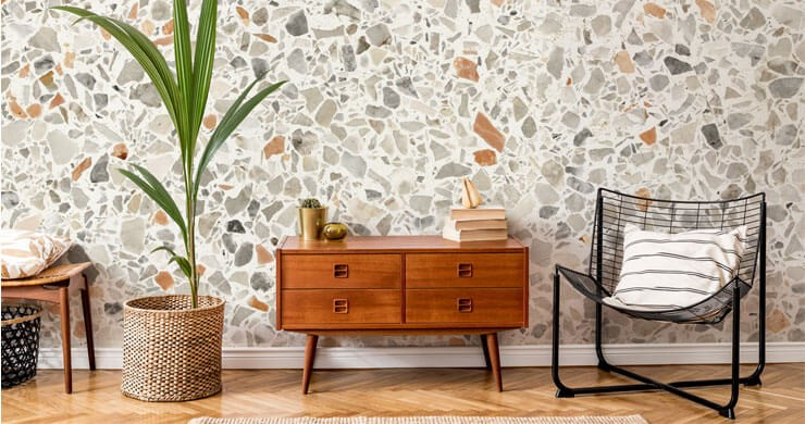 terracotta, grey and off-white terrazzo wallpaper in room with mid-century wooden drawers and green plant