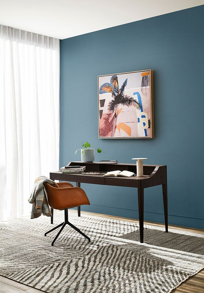 inky-blue painted walls in sleek office with wooden desk and colourful wall art