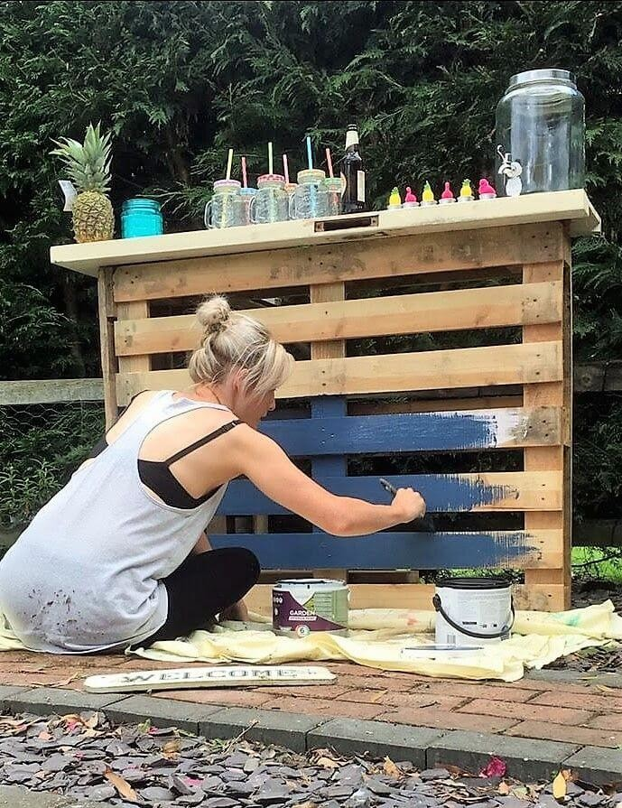 blonde woman painting pallet bar navy blue