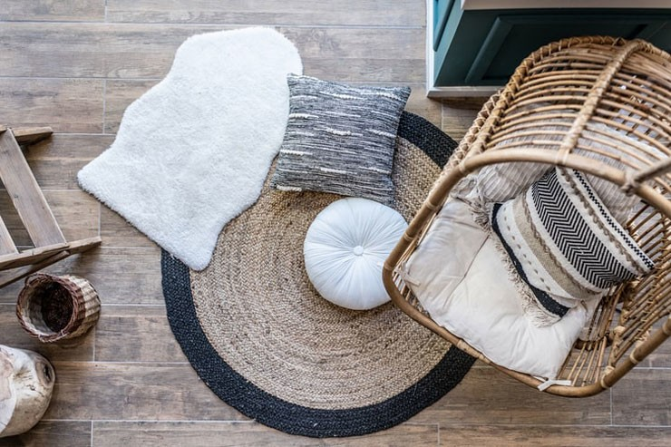 boho wicker hanging chair and an assortment of rugs and cushions