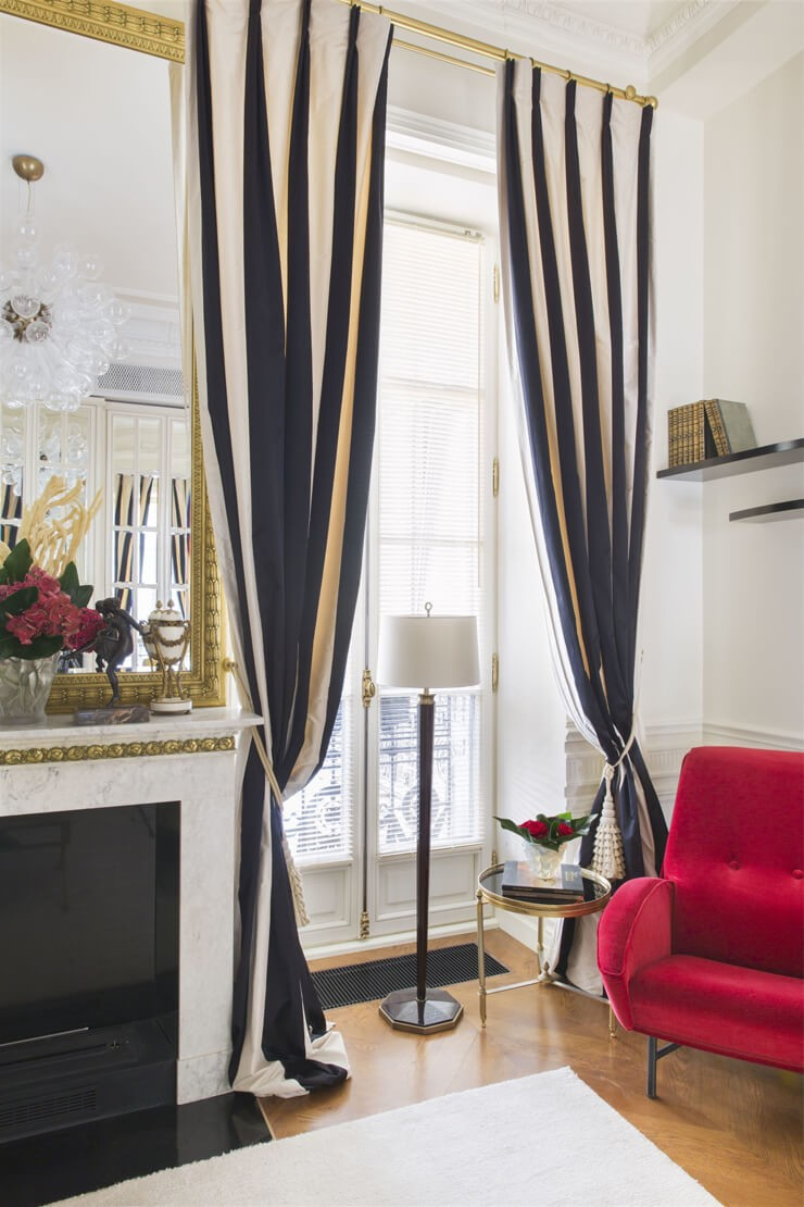 black and white striped curtains in white room with lipstick red chair