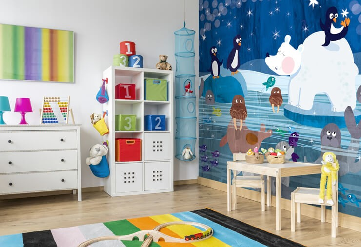 polar bear, penguins, walrus and seal illustration mural in child's bedroom with play mat, drawers and a drawing table