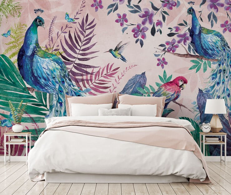pink wallpaper set in jungle with peacocks, a parrot, a hummingbird and flowers wallpaper in master bedroom with white and pink bed