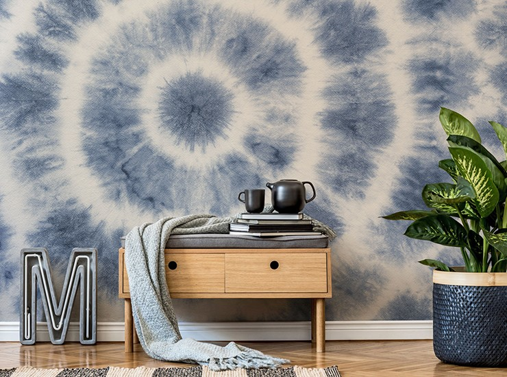 tie dye blue and white wallpaper in lounge with natural wooden drawers and a tropical potted plant
