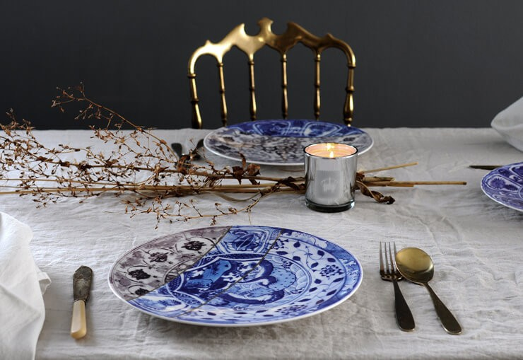 blue and white oriental plate fixed with gold lines on table with other plates, white table cloth and dried floral decoration centrepiece
