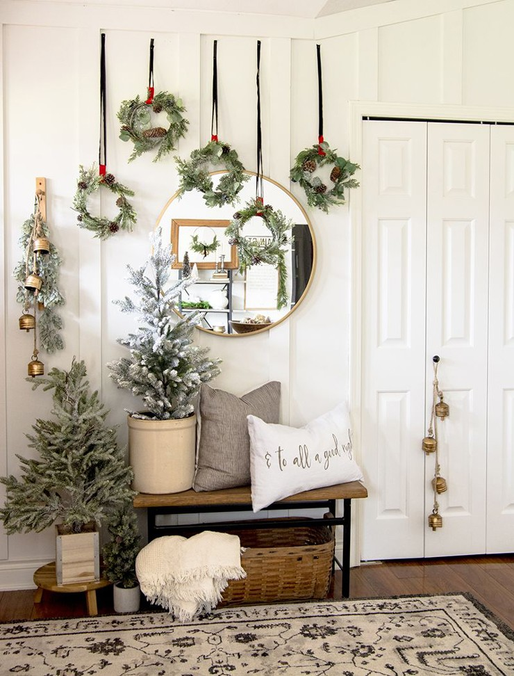 white Scandi hallway with wall wreath decorations, bells and Christmas trees