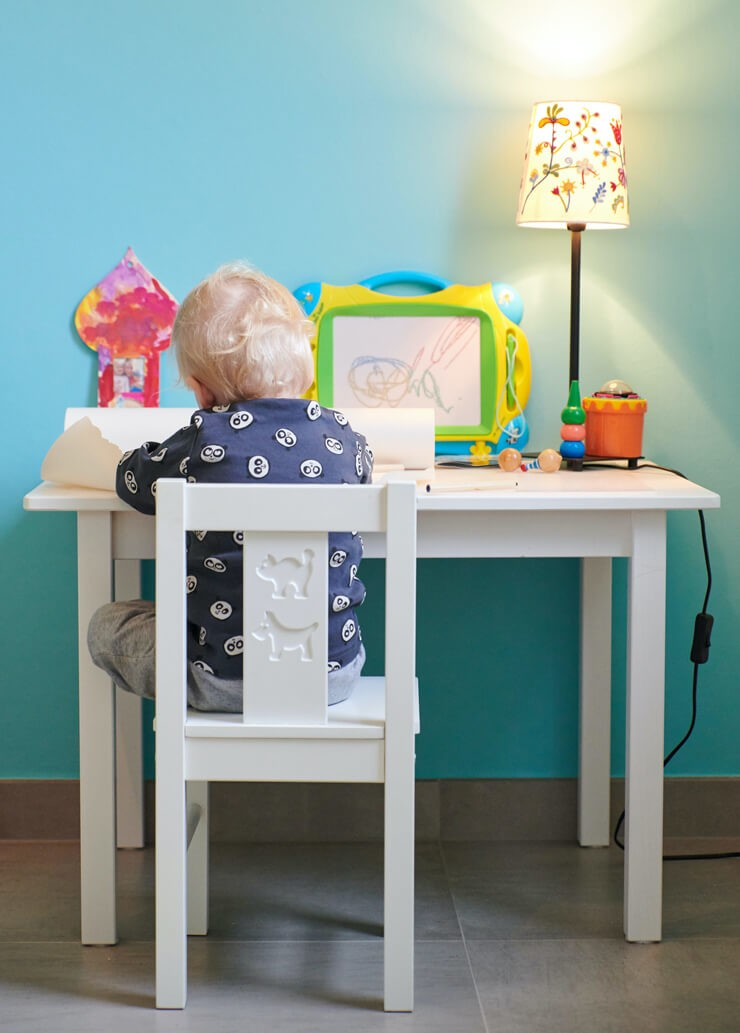 blonde haired toddler sat at white desk with flower lamp