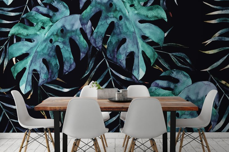 dark leaf wallpaper behind dining table and chairs