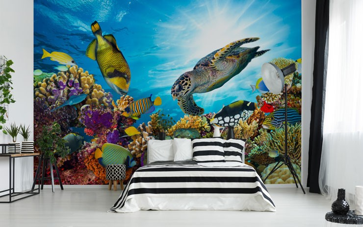 fish, turtle and coral wallpaper in open loft apartment with stripey black and white bed