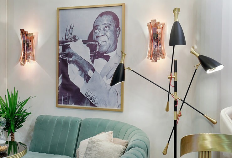 room with bleu sofa, rose gold wall scones and gold and black lamp with louis armstrong print