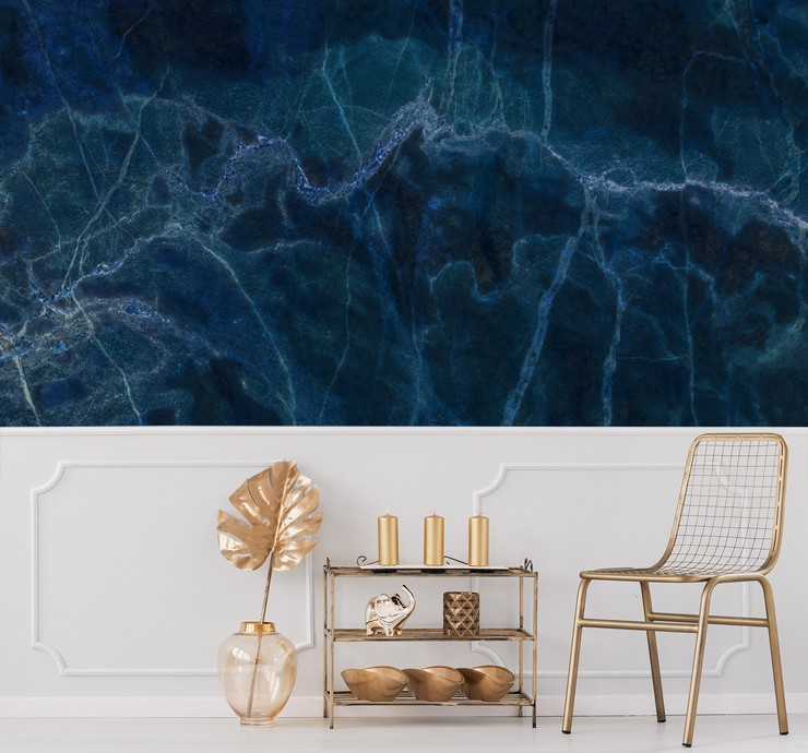 inky blue marble wall mural above white panelling in lounge with gold decor