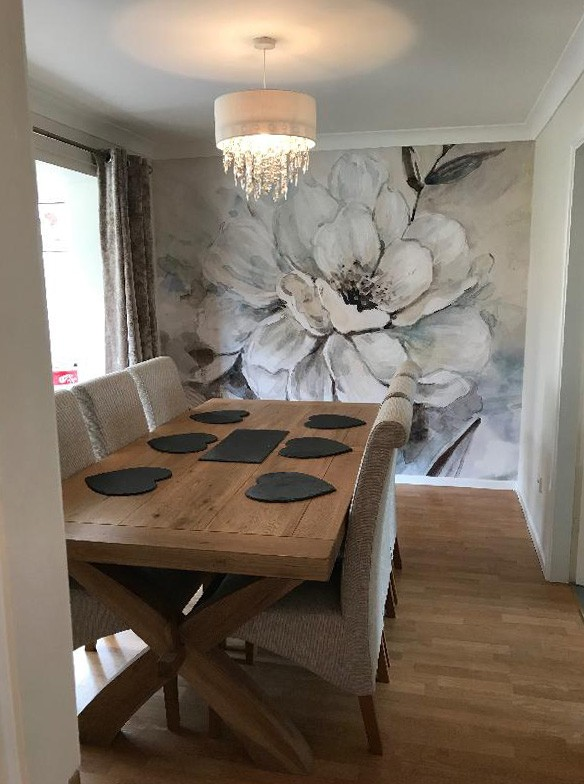 grey and off-white painted floral wallpaper in dining room with wood dining table