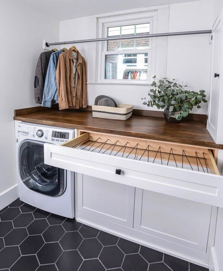 white and wooden drying drawer in small laundry room under window