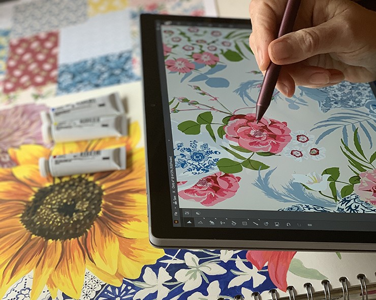 artist's hand drawing a floral pattern on an iPad
