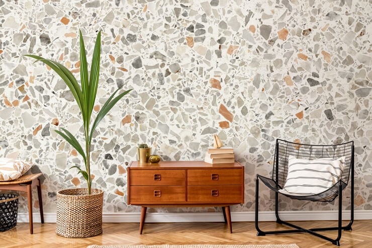 rusty brown, grey and off-white terrazzo wallpaper in lounge with wooden furniture and black metal chair