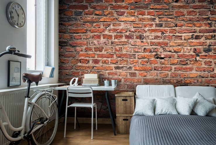 red brick wall in trendy grey and white bedroom